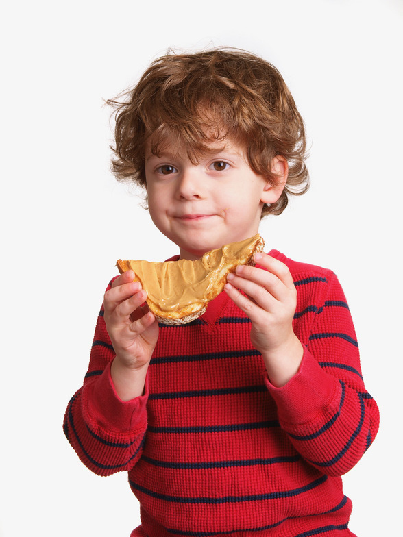 A boy eating bread and peanut butter