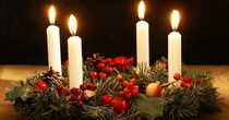Four lit advent candles with a wreath