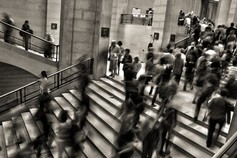 Black and white image of people walking in underground