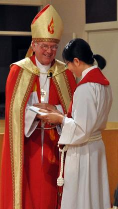 As the congregation applauds bishop michael welcomes vivian with a handshake